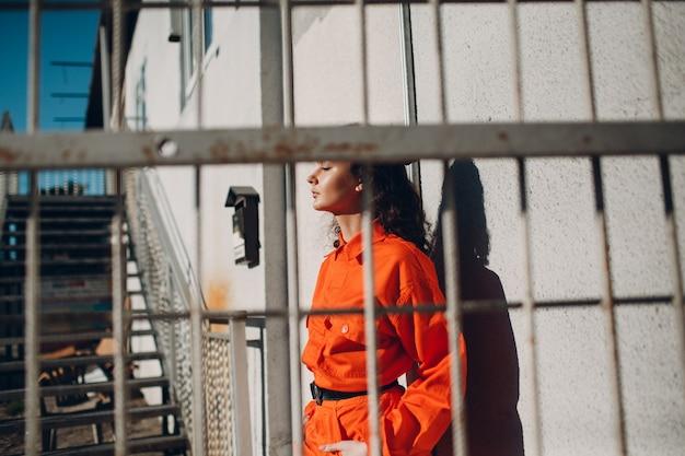 Jonge brunette krullend vrouw in oranje pak achter kooi. wijfje in kleurrijk overallportret.