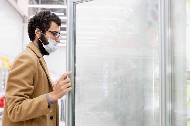 Jonge brunette man in een medisch masker in de supermarkt op de afdeling met diepvriesproducten. coronapandemie. ruimte voor tekst.
