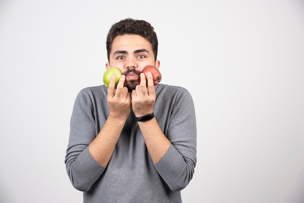 Jonge brunette man met appels dicht bij zijn gezicht.