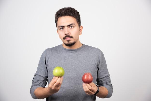 Jonge brunette man met twee appels op grijs.