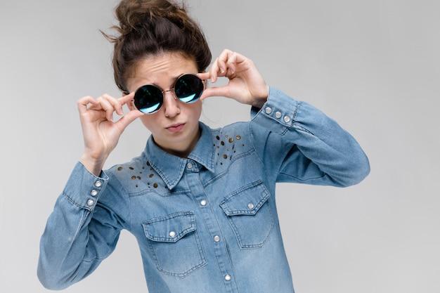 Jonge brunette meid in ronde glazen. haren zijn verzameld in een knot. het meisje blijft haar bril rechttrekken.