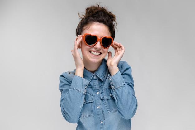 Jonge brunette meid met een bril in de vorm van een hart. de haren zijn verzameld in een knot. het meisje stelt haar bril af.