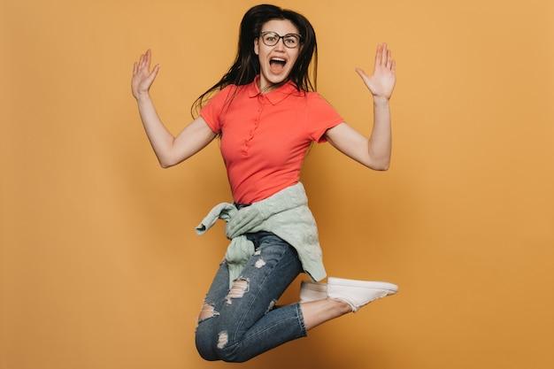 Jonge brunette meisje in glazen, het dragen van rode t-shirt, jeans, trui vastgebonden in de taille en witte sneakers, hoog springen, schreeuwen, haar handen omhoog, over gele achtergrond.