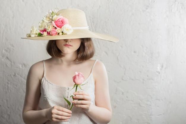 Jonge brunette meisje in hoed met bloemen