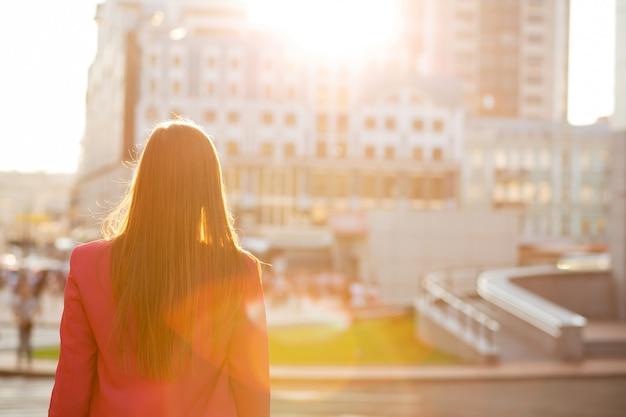 Jonge brunette meisje kijken naar de gebouwen van de stad met zacht zonlicht. achteraanzicht. ruimte voor tekst