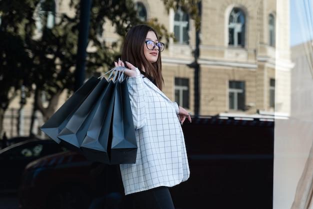 Jonge brunette meisje met boodschappentassen. mooi meisje in de buurt van een modewinkel na het winkelen. zwarte vrijdag.