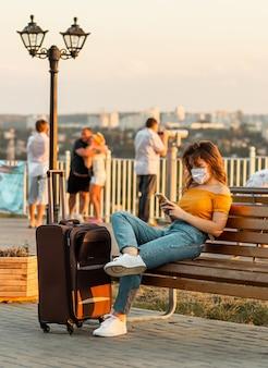 Jonge brunette meisje met een chirurgisch masker browsen door haar telefoon zittend in het park met haar koffer in de buurt van haar.