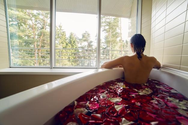 Jonge brunette meisje met lang haar is een wit bad met rozenblaadjes en kijkt uit het grote raam waarachter bomen staan