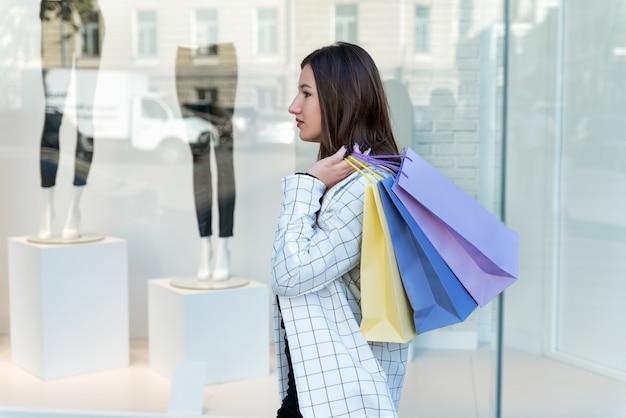 Jonge brunette meisje met veelkleurige boodschappentassen in winkelcentrum. winkelen.