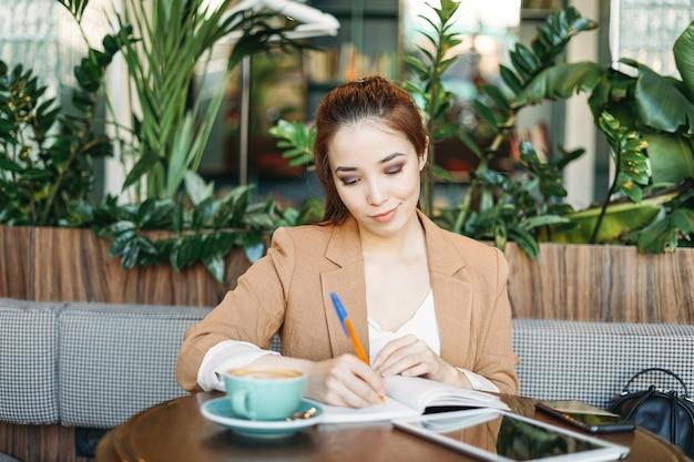 Jonge brunette meisje student huiswerk in notitieblok met koffie met behulp van tablet in café