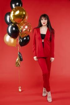 Jonge brunette model in rode kostuum poseren in de buurt van ballonnen