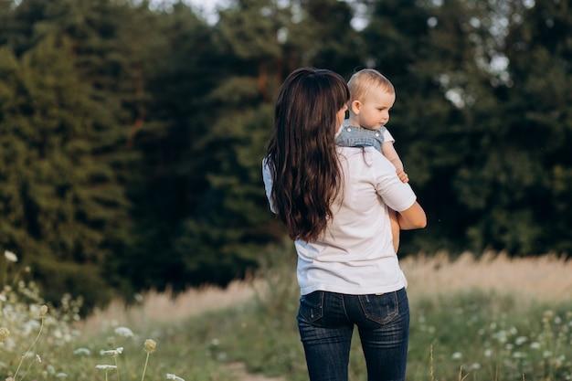 Jonge brunette moeder loopt met haar dochtertje over het veld