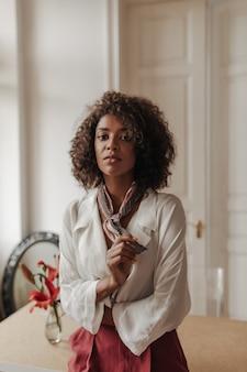 Jonge brunette mooie krullende vrouw in bordeauxrode broek en witte blouse kijkt naar voren, leunt op houten tafel in een gezellige kamer