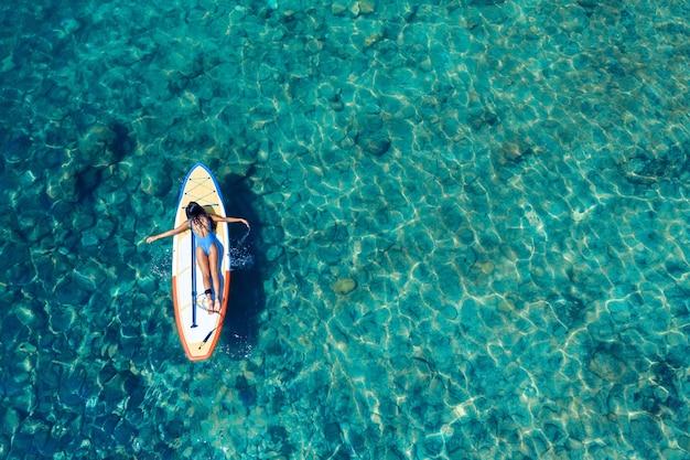 Jonge brunette op een surfplank