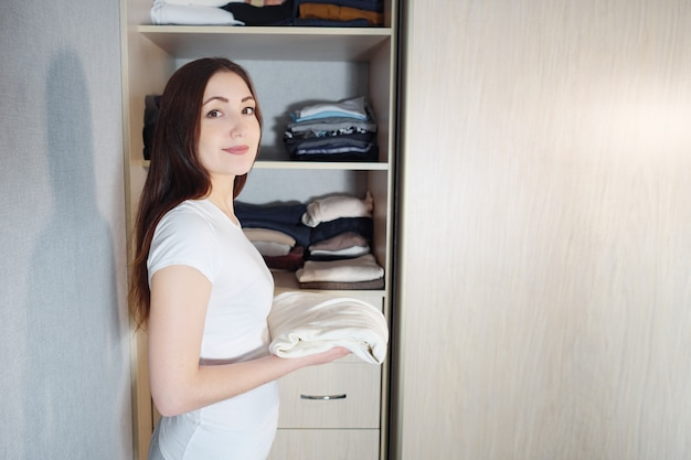 Jonge brunette op plank van kledingkast met stapel verschillende kleding thuis, kijkend naar camera