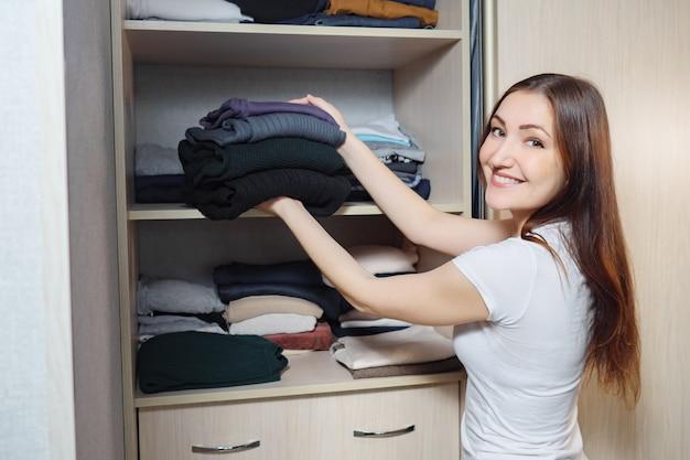 Jonge brunette op plank van kledingkast met stapel verschillende kleding thuis