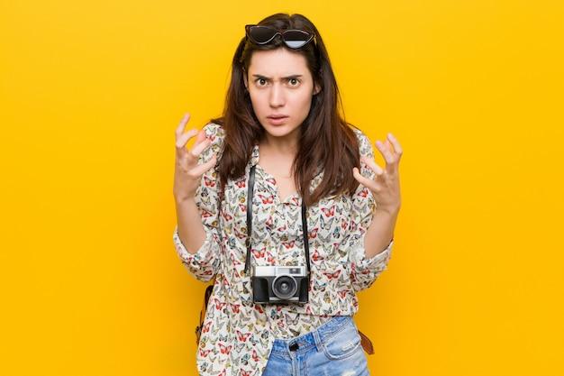 Jonge brunette reiziger vrouw boos schreeuwen met gespannen handen