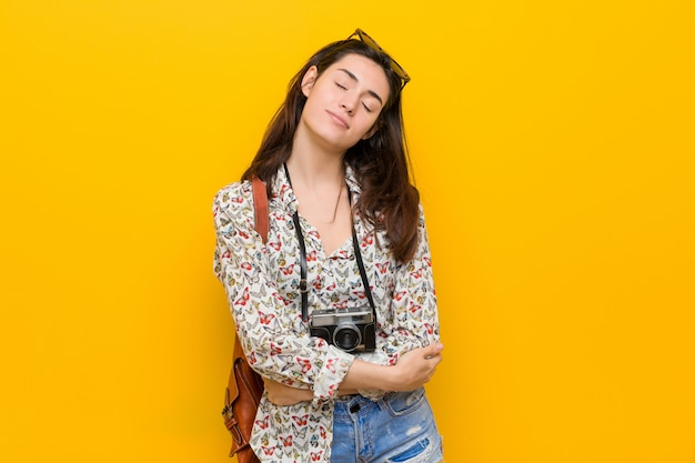 Jonge brunette reiziger vrouw knuffels, glimlachend zorgeloos en gelukkig.