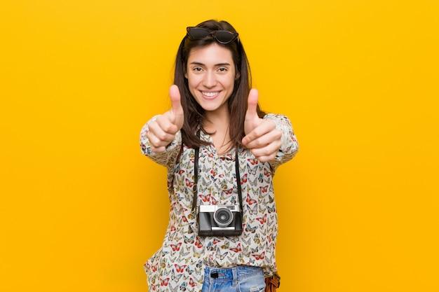 Jonge brunette reiziger vrouw met thumbs ups, cheers over iets, steun en respect.