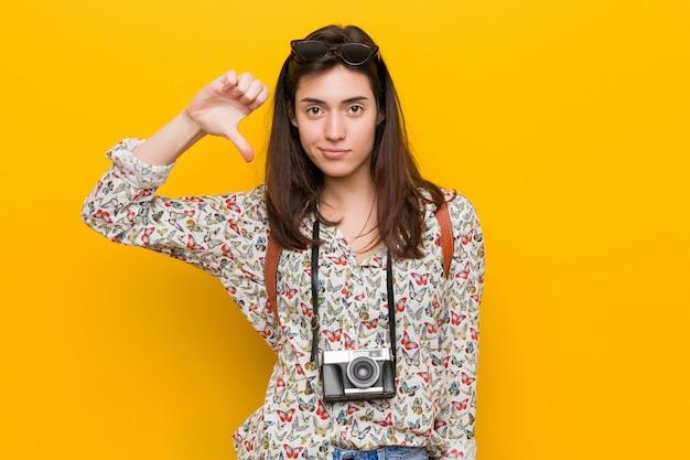 Jonge brunette reiziger vrouw toont een afkeer gebaar, duimen naar beneden. onenigheid .