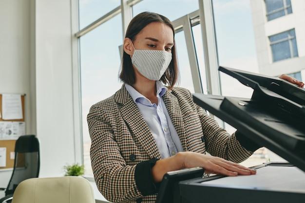 Jonge brunette secretaresse in formalwear en beschermend masker permanent door xerox machine in kantoor en kopieën van documenten maken