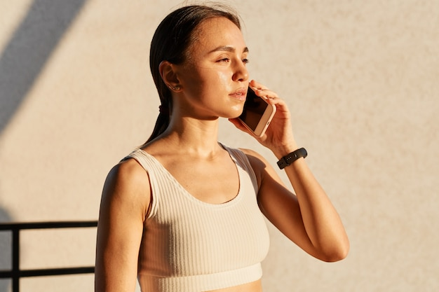 Jonge brunette sportieve meid praten op de smartphone in de buurt van de grijze muur, gekleed in een witte sportieve top, wegkijkend met zelfverzekerde en geconcentreerde uitdrukking.