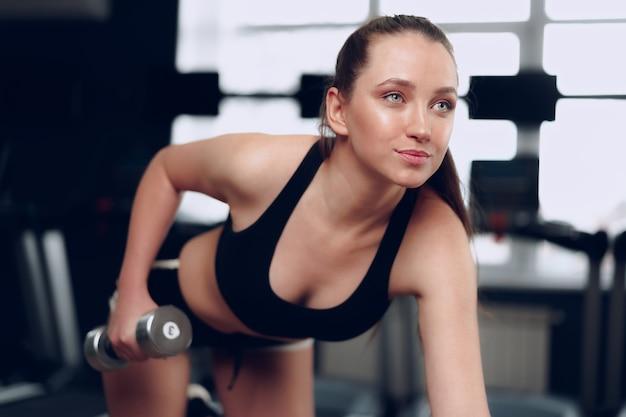 Jonge brunette sportieve vrouw trainen met halter in een sportschool