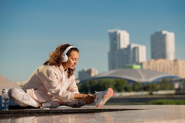 Jonge brunette sportvrouw in activewear en koptelefoon been strekken tijdens het trainen op marmeren structuur in stedelijke omgeving