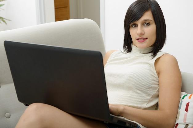 Jonge brunette student zittend op de bank met een laptop