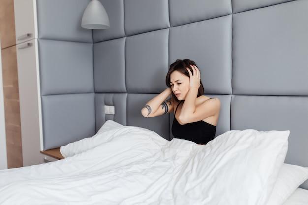 Jonge brunette toont ongezonde blik in de ochtend na het slapen in haar brede bed