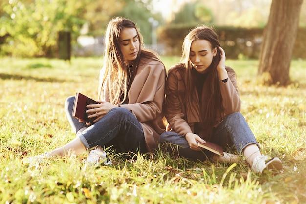 Jonge brunette tweelingzusjes zitten dicht bij elkaar met gesloten ogen op het gras, benen licht gebogen in de knieën en gekruist, met bruine boeken, casual jas dragen in herfst park op achtergrond.