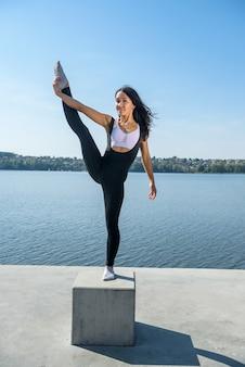 Jonge brunette vrouw beoefenen van yoga vroeg in de ochtend voor werktijd. concept van wellness en een gezonde levensstijl