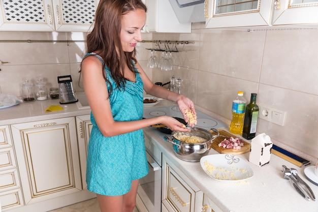 Jonge brunette vrouw besprenkelt geraspte kaas op pasta in pot tijdens het bereiden van huisgekookte maaltijd voor het diner in de keuken