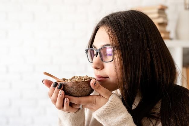Jonge brunette vrouw brouwen van koffie in coffemaker, groene koffiebonen ruiken