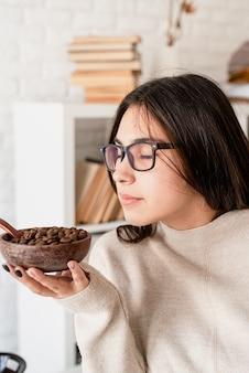 Jonge brunette vrouw brouwen van koffie in coffemaker, koffiebonen ruiken