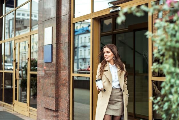 Jonge brunette vrouw buitenshuis. straat foto. kartonnen kopje koffie in de handen. herfst mode. beige jas, modieuze rok en hoge laarzen. het gelukkige glimlachende meisje lanceert de treden.
