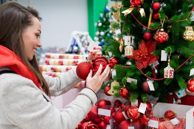 Jonge brunette vrouw die kerstversieringen kiest en winkelt op de kerstboom op de markt