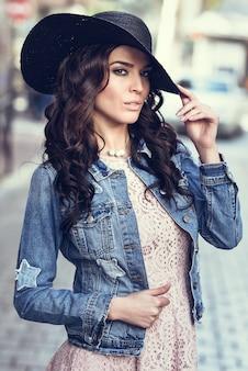 Jonge brunette vrouw die zich in de stedelijke achtergrond bevindt.
