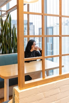 Jonge brunette vrouw drinkt koffie en kijkt peinzend uit het raam van de straatbar terwijl ze haar tijd alleen doorbrengt