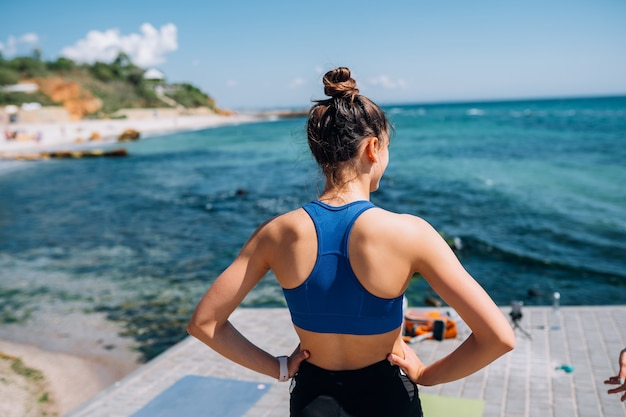Jonge brunette vrouw fitness outfit dragen, die zich uitstrekt op pier