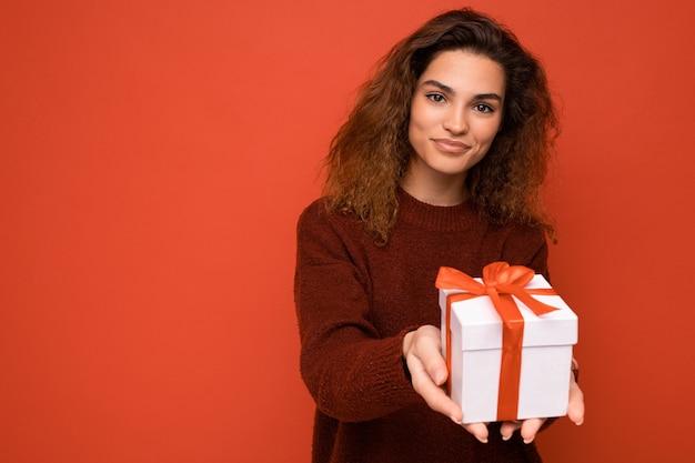 Jonge brunette vrouw geïsoleerd over kleurrijke achtergrond muur dragen alledaagse trendy outfit houden geschenkdoos en kijken naar camera. kopieer ruimte, mockup
