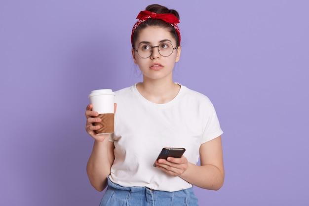 Jonge brunette vrouw geïsoleerd over lila ruimte met koffie om mee te nemen en mobiel terwijl ze aan iets denkt