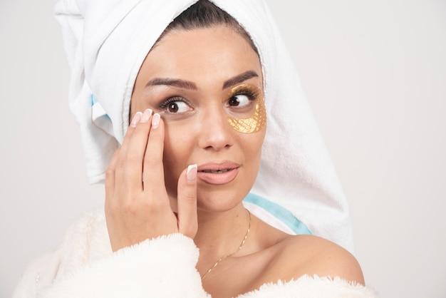Jonge brunette vrouw, gekleed in badjas met cosmetische ooglapjes
