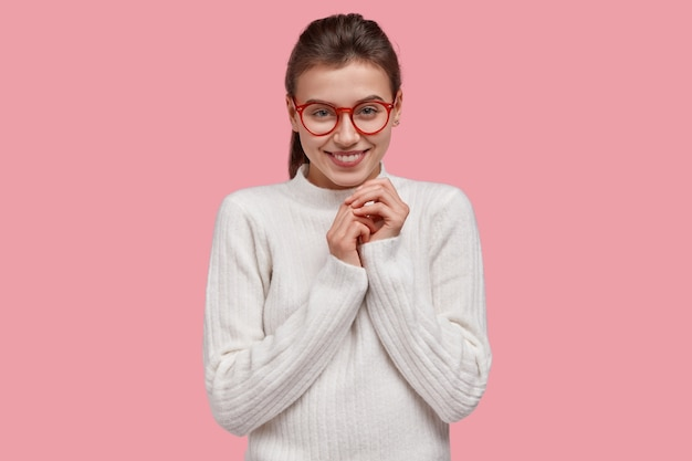Jonge brunette vrouw, gekleed in witte trui en rode bril