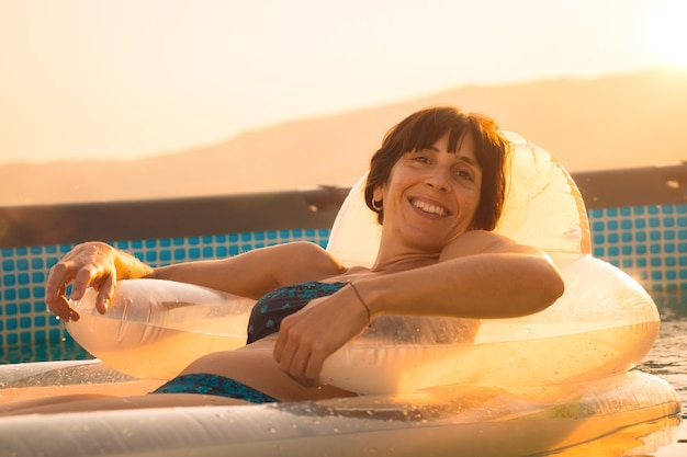 Jonge brunette vrouw genieten van de zomer op een mat in het zwembad