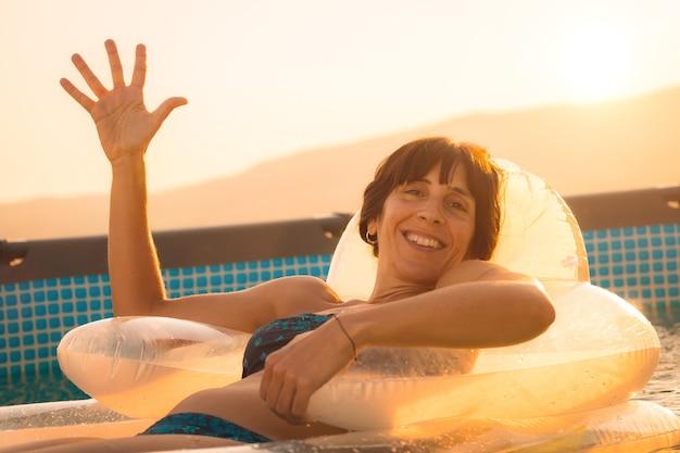 Jonge brunette vrouw genieten van de zomer op een mat in het zwembad Premium Foto