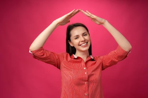 Jonge brunette vrouw hand in hand boven het hoofd als dak tegen roze achtergrond