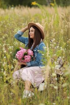 Jonge brunette vrouw in denim jasje, roze jurk en hoed met boeket roze bloemen