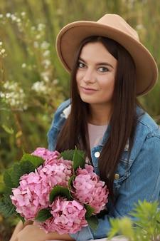 Jonge brunette vrouw in denim jasje, roze jurk en hoed met boeket van roze bloemen hortensia zittend in veld op zomerdag.