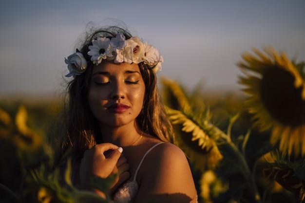 Jonge brunette vrouw in een kroon van bloemen met gesloten ogen genieten van de zon in een zonnebloem veld